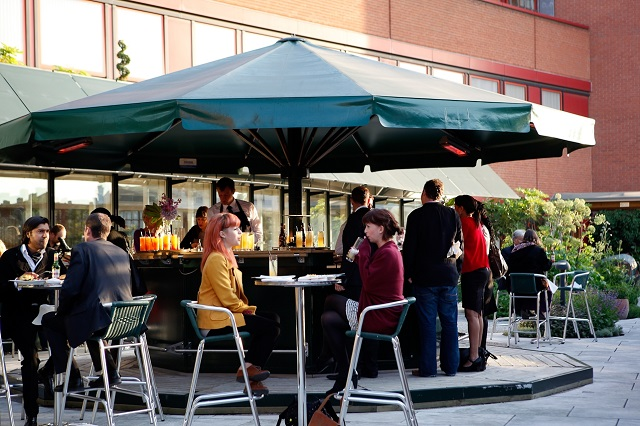 British Library Summer Party NW1. Terrace bar with guests enjoying a drink outside in the sun.