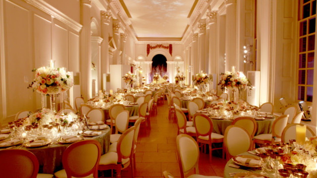 Orangery set for a dinner party with formal seating and round tables in rows with floral centre pieces and large floor to ceiling windows on one side Kensington Palace Christmas Party W8