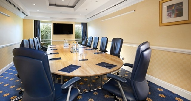 The Medway Suite set for a conference event with an oval boardroom table in the centre of the room with a tv screen on the wall either side of the windows Hilton Maidstone Venue Hire ME14