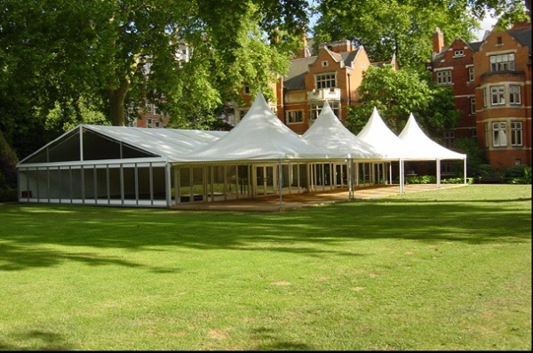 College Garden Marquee set for a summer party with inside sheltered space and outside terrace area, views of the venue behind and lawns in front Westminster Abbey Summer Party SW1