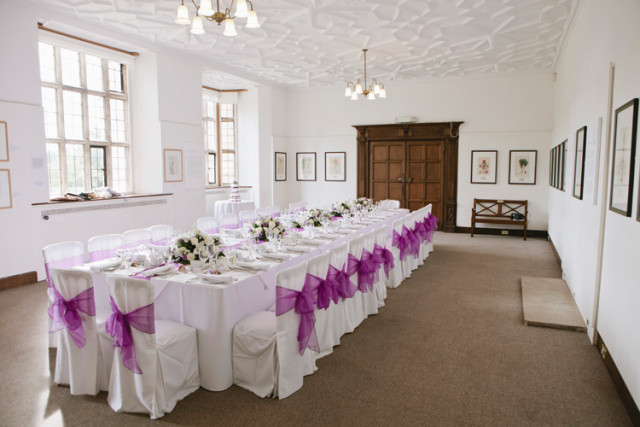 Gallery set for a wedding breakfast with natural daylight and long banqueting table dressed in white linen and chair covers with bows Wakehurst Place Summer Party RH17
