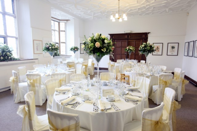 Gallery set for a formal dinner with round tables dressed in white linen with large floral centre pieces and natural daylight Wakehurst Place Christmas Party RH17
