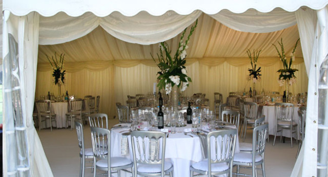 Marquee set for a dinner with round tables with floral centre pieces under the marquee Wakehurst Place Summer Party RH17