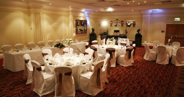 Wembley Suite with round tables set for a wedding with round tables dressed in white linen and chairs with white chair covers with bows on the back with tables facing the top table Hilton Nottingham Venue Hire NG1
