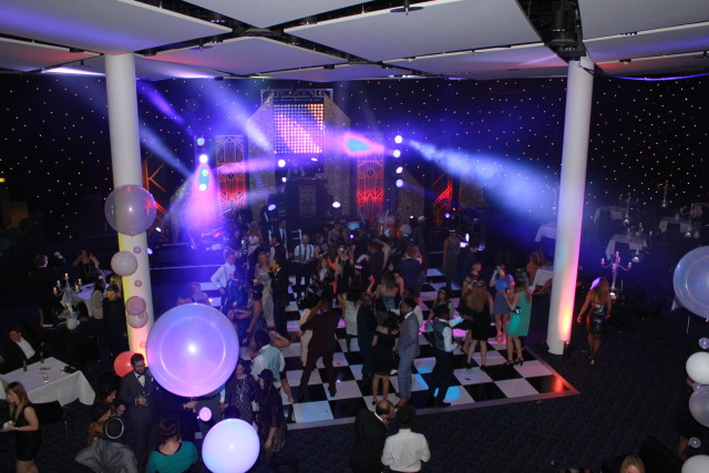 Bobby Moore Room with dance floor centred in the room between pillars and guests enjoying a dance Wembley Stadium Christmas Party HA9