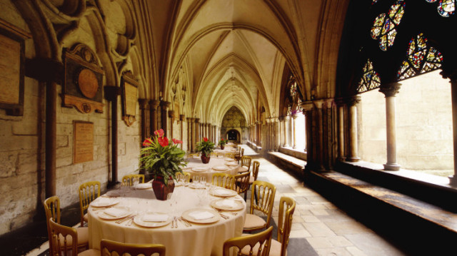 East Cloister set for a dinner with round tables dressed in white linen and floral table decorations with grand stone atch ways and natural daylight Westminster Abbey Venue Hire SW1