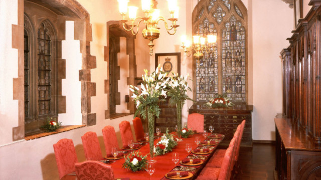 Cheneygates set for an intimate dinner with bright red tables and floral decorations on the table and mozaic windows Westminster Abbey Venue Hire SW1