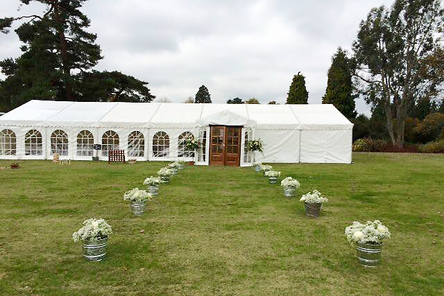 Marquee view from outside with pathway marked out with flowers towards the entrance Wakehurst Place Summer Party RH17