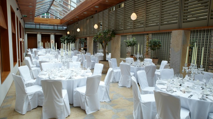Adam Hall set for a party with white linen over round tables and chair covers Compton Verney Christmas Party CV35