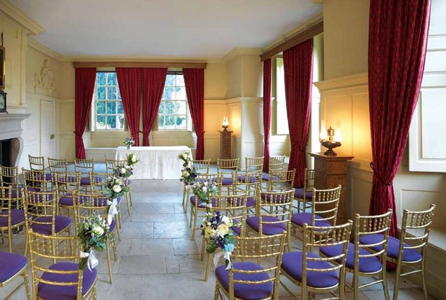 Charlotte's Cottage set for a wedding ceremony with floral bouquets decorating the chairs that lead up to the grand floor to ceiling windows Kew Palace Venue Hire TW9
