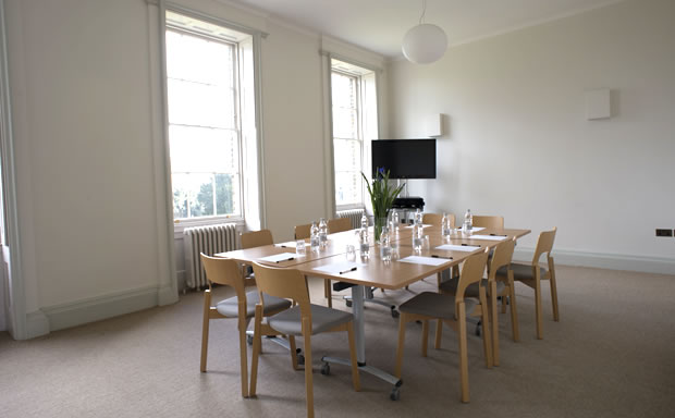 Church Room set for a small boardroom meeting with large windows for natural daylight and TV screen Clissold House Venue Hire N16