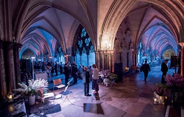 Cloisters set for a drinks reception with high arched exposed brick ceilings illuminated with bright uplightesrs Westminster Abbey Christmas Party SW1