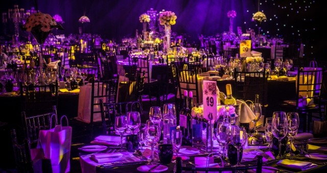 Deansgate Suite set for a large christmas party with high ceilings projecting light patterns, large screens on the walls and round tables set for dinner Hilton Manchester Deansgate Christmas Party M3