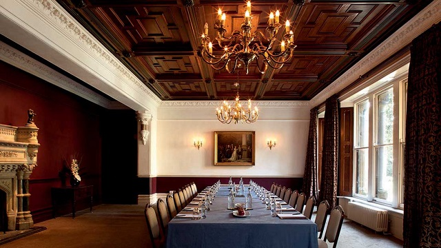 Ettington Park Hotel Christmas Party CV37. large dining table in historic building with chanderlier and wooden ceiling