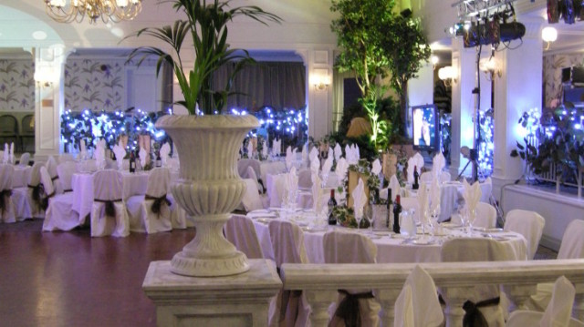 Garden Suite set for a large dinner with floral decor on the tables and surrounding the room with white linen dressed on the oval tables with blue uplighters Birmingham Botanical Gardens Christmas Party B15