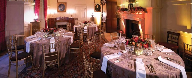 Kings Dining Room set for a private dinner with round tables in the historic room with open fire place and wall paintings Kew Palace Christmas Party TW9