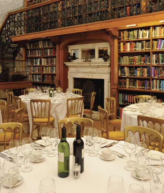 Library One with round tables dressed in white linen with wine in the centre of the tables and views of library book cases Birdcage Walk Christmas Party SW1