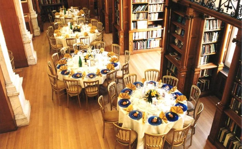 Library One with round tables dressed in white linen with floral centre pieces and views of library book cases Birdcage Walk Christmas Party SW1