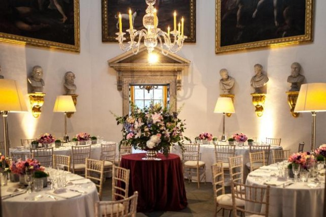 Long Gallery with round tables set for dining with high circular walls with portrait paintings hanging from them and large candelabra chandelier hanging Chiswick House Christmas Party W4