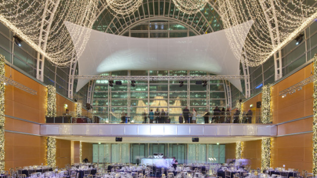 Main Hall set for a large christmas party with views of the glass wall and ceiling backdrop with a standing drinks reception in the gallery with round tables set for dinner in the main hall East Wintergarden Christmas Party E14