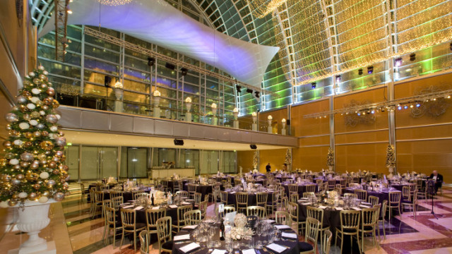 Main Hall set for a christmas dinner with round tables set for dinner with glass ceiling and walls East Wintergarden Christmas Party E14