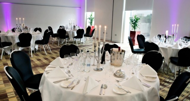 Meeting Room set for a dinner with round tables dressed with white linen and candles with lots of natural daylight Hilton Manchester Deansgate Venue Hire M3
