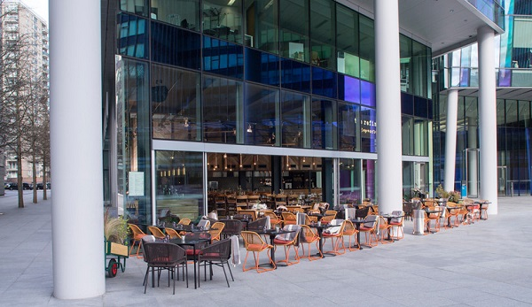Refinery Regents Place Summer Party NW1. Outside space in the evening sun with tables and chairs outside.