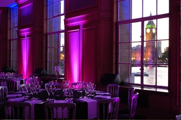 River Rooms set for an evening dinner with formal round tables dressed in linen and purple uplighters next to the windows Venue Hire SE1