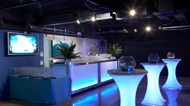 Atlantic Cove set for a drinks reception with poseur tables illuminated in bright lights London Aquarium Venue Hire SE1