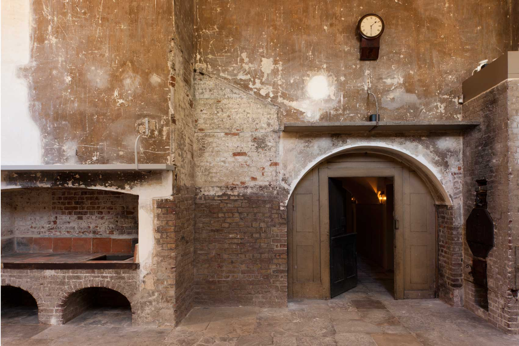 Royal Georgian Kitchens displaying weathered exposed brick work and open oven with high arched doorways Kew Palace Venue Hire TW9