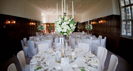 Dining Room set for a formal dinner with candelabras in the centre of the round tables with floral decor Wakehurst Place Venue Hire RH17