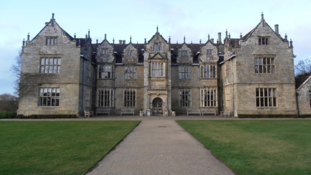 Exterior view of the venue with grand drive way and lawns either side Wakehurst Place Venue Hire RH17