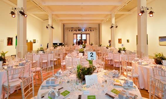 Gallery 3 set out for a Christmas party with rounds tables dressed in white linen set in the middle of the room with white walls and pillars with light rigging hanging from them Whitechapel Gallery Christmas Party E1