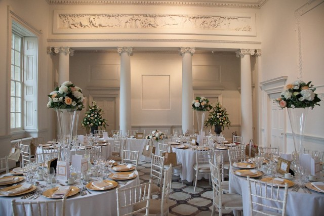 Adam Hall set for a party with floral centre pieces and round tables with pillars in the background Compton Verney Christmas Party CV35