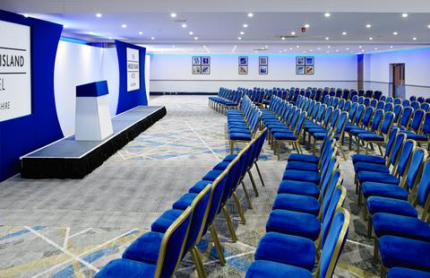 Paris Suite set for a large conference with chairs set in theatre style facing a stage with a lectern on it Jurys Inn Hinckley Island Hotel Venue Hire LE10