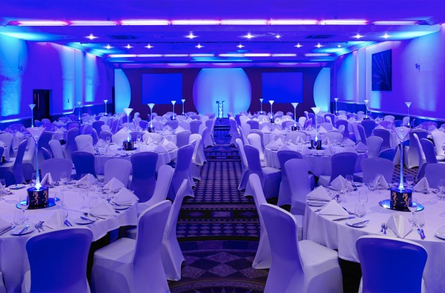 Function Room set for a large christmas party with round tables dressed in white linen with matching chair covers with blue uplighters in the ceiling Jurys Inn Hinckley Island Hotel Venue Hire LE10