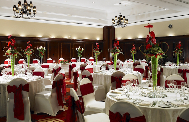 Leeds Marriott Christmas Party SL1. Spacious layout with white table cloth and red ribbon decorating chairs and red high flowers in centre of tables for a festive feel.