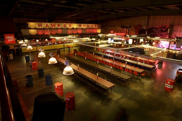 Big Room Hawker House with rows of benches in the centre of the room surrounded by street food stalls Christmas Party SE16