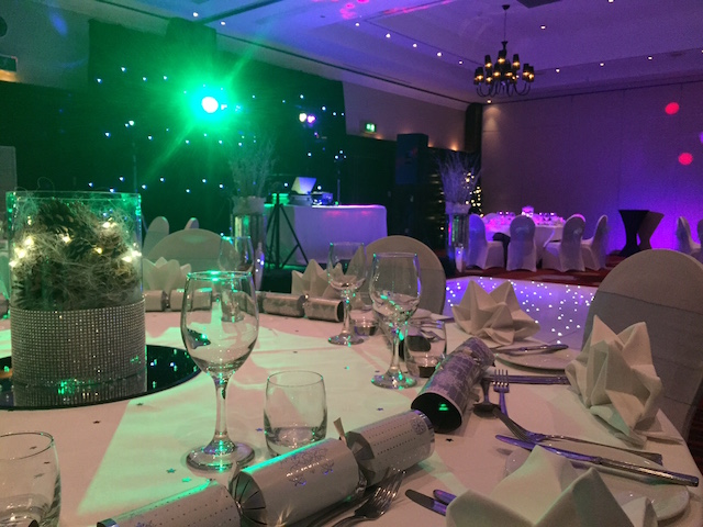 Leeds Marriott Christmas Party SL1. Christmas party event. large round tables with chairs and festive centre pieces and disco lights on.