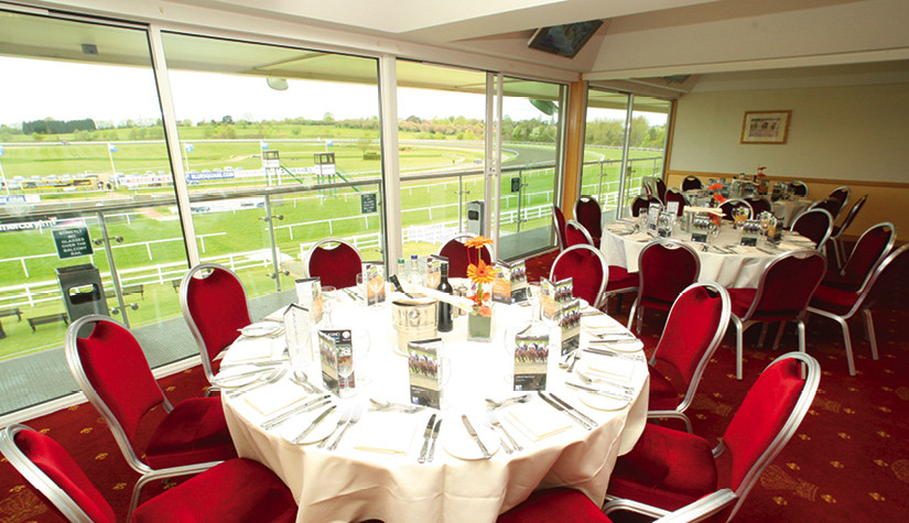 Grand Stand set for a dinner with round tables dressed in white linen with views over the racecourse Lingfield Park Hotel & Country Club Venue Hire RH7