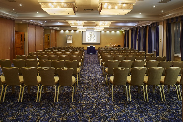 Rembrandt Hotel Venue Hire SW7. Conference room set out, theatre style. With blue carpet and gold chairs with an elegant feel.