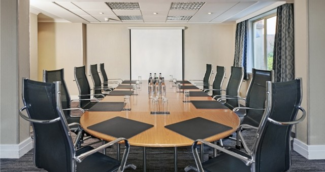 Meeting Room set for a conference with oval boardroom table and high back chairs tucked in around it with large presentation screen at the front of the room Hilton St Anne's Manor Venue Hire RG40
