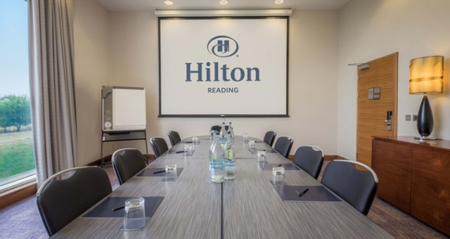 Meeting Room set up for a meeting in boardroom style with natural daylight and presentation facilities on the wall Hilton Reading Venue Hire RG2