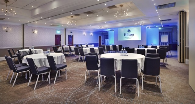 Meeting Room set for a large conference with tables and chairs set in cabaret style all facing a front projector Hilton St Anne's Manor Venue Hire RG40