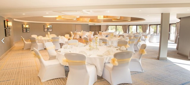 Circular, light and airy Function Room set for a wedding with round tables set with white table linen and matching chair covers with yellow bow Jurys Inn Hinckley Island Hotel Venue Hire LE10