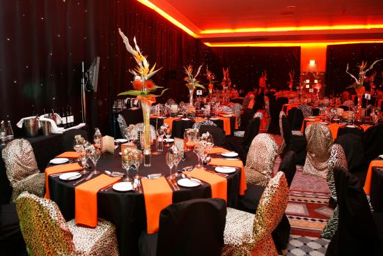 Function Room set for a large christmas party with brightly coloured table linen and large extravagant centre pieces on round tables with blackout blinds surrounding the room Jurys Inn Hinckley Island Hotel Venue Hire LE10