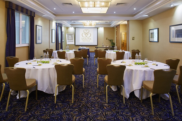Rembrandt Hotel Venue Hire SW7. Conference set out for guests. round tables with chairs around and screen ahead for presentation.