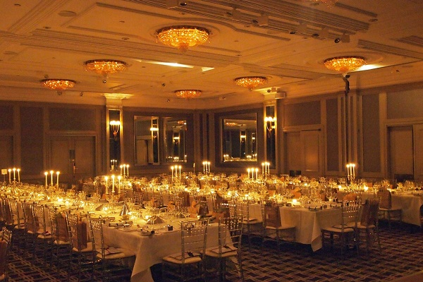 Hyatt Churchill Christmas Party W1H. evening dining in large ballroom with festive lighting and long tables set up for guests to sit and dine