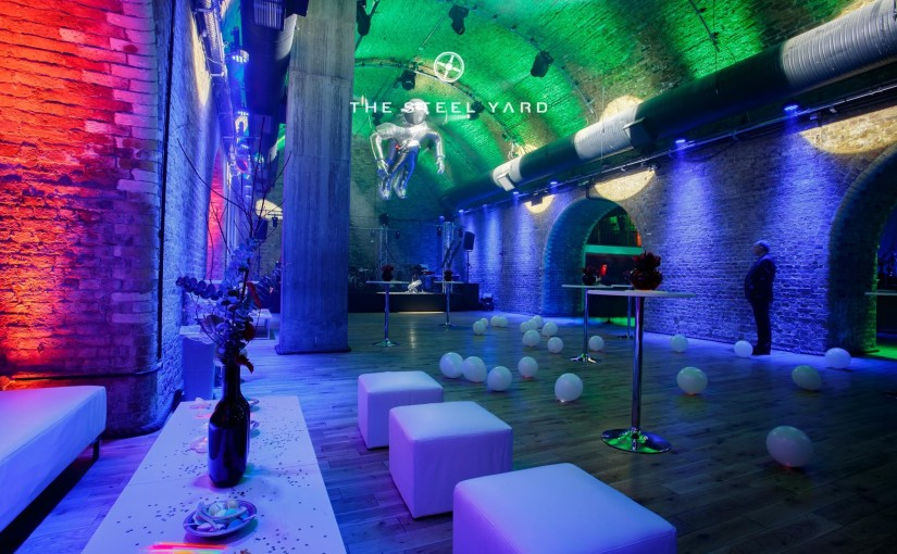 a long shot look down the brick archway some white stolls on the left balloons on the floor and a giant inflatable spaceman hanging from the ceiling in silver