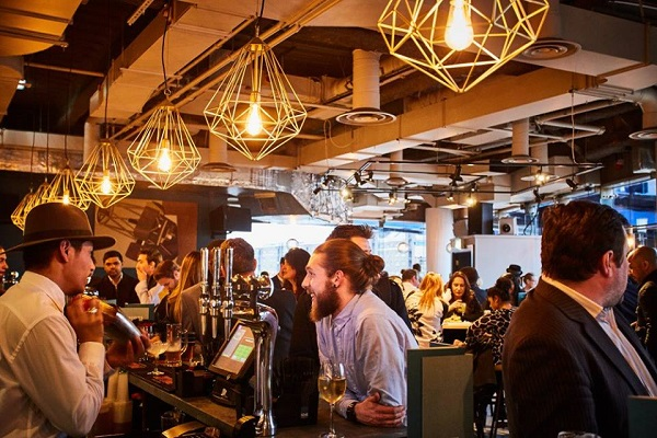 Brodies Bar and Kitchen Venue Hire E14. Cool lighting and industrial feel of furnishings with guests enjoying their evening at the bar being served